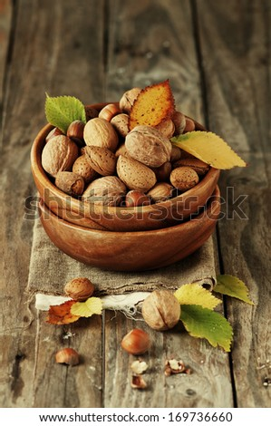 Almond, nuts and walnut on the wooden table, selective focus and retro style - stock photo