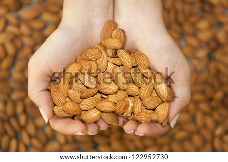 Almond nuts in the woman's hands forming heart shape - stock photo