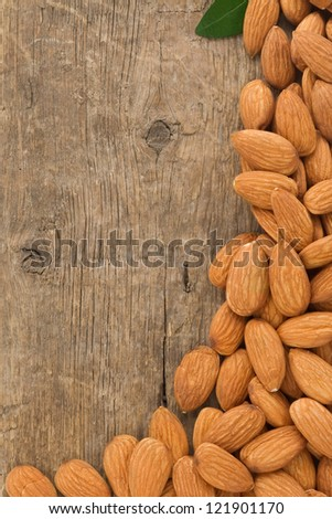 almond nuts on wood background - stock photo