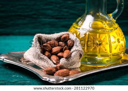 almond oil  on wooden table - stock photo