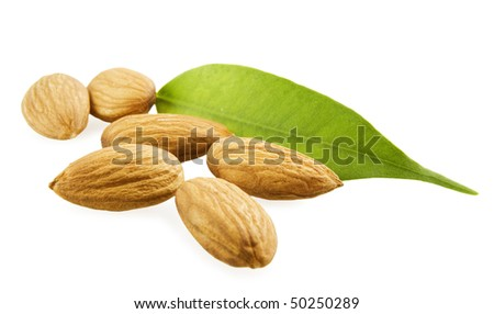 Almonds and a green leaf on a white background