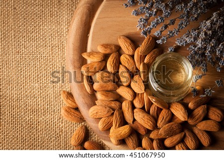 Almonds and almond oil on wooden background. Skin and hair care concept. Lavender and nuts. - stock photo