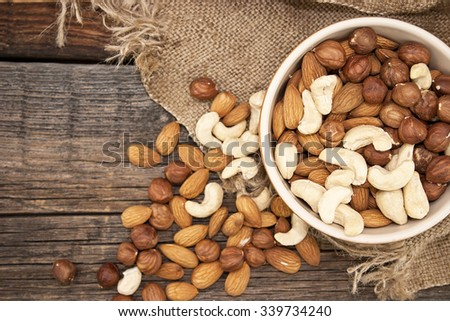 Almonds, cashew and hazelnuts in ceramic bowl on a rustic wooden background. Top view. Healthy concept. - stock photo