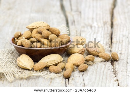 almonds in a bowl on old wooden background - stock photo