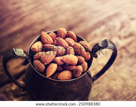 Almonds in a coper old style vase, on old wooden table background - stock photo