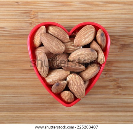 Almonds in a heart bowl. Close-up.