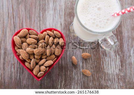 Almonds in a red heart shaped bowl with a glass of almond milk on wood background