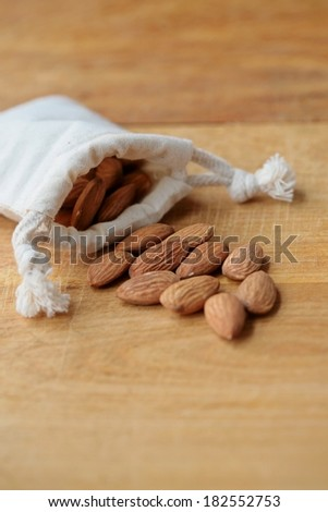 Almonds in a small sack bag on wooden background. Selective focus.