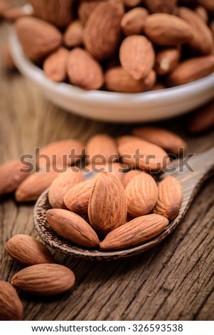 almonds in a white ceramic bowl on grained wood background