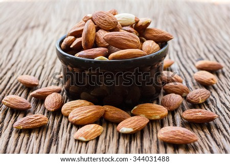 Almonds in black bowl on almonds background - stock photo