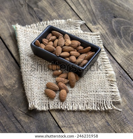 almonds in  bowl on grained wood background, close up - stock photo