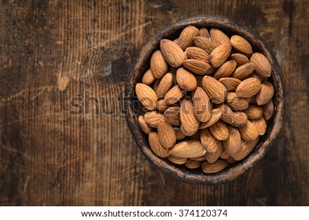 Almonds in brown bowl on textured wooden background, top view. Copy space on left side - stock photo