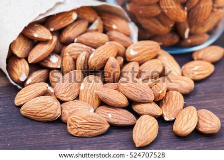 Almonds in brown paper bag and glass on grunge wooden background.