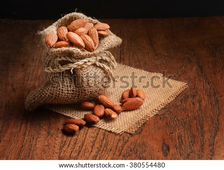 Almonds in burlap bag with almonds spilling out on wood table.