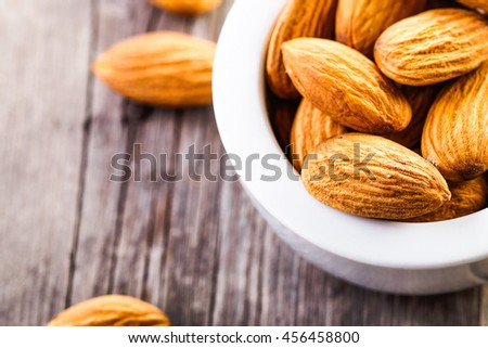 almonds in ceramic bowl on wooden background