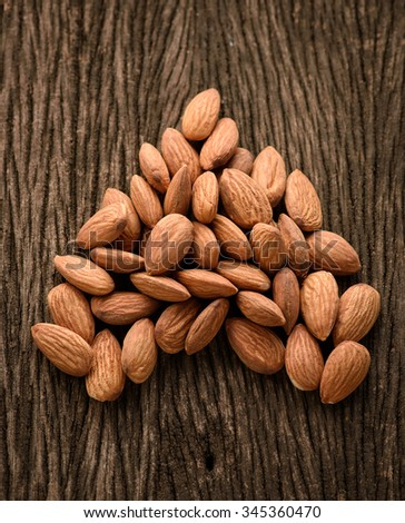 Almonds in heart shape on wood background - stock photo