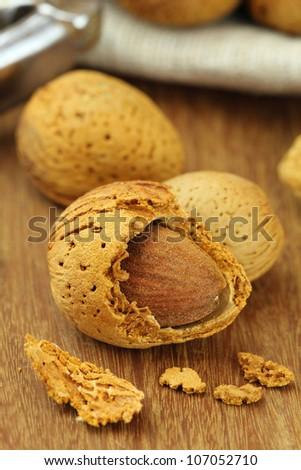Almonds in kernel on a wooden surface with a nutcracker at the background