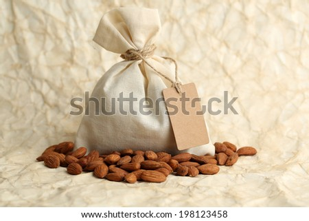Almonds in sack with tag on old paper background - stock photo