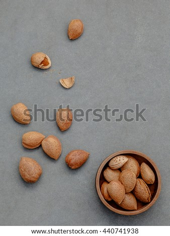 Almonds kernels and whole almonds on concrete background. Whole and chopped almond on concrete background.  - stock photo