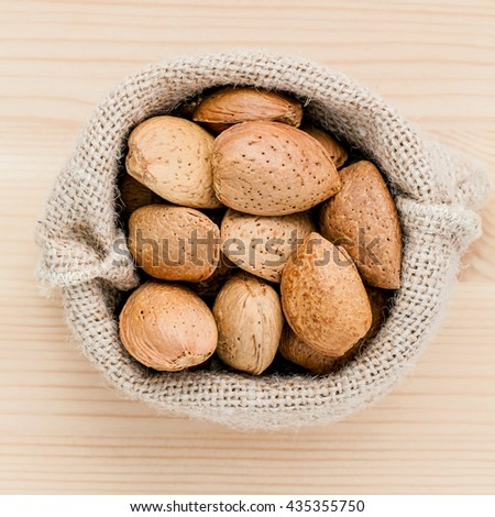 Almonds kernels and whole almonds on wooden background. Whole and chopped almond on wooden background. almond kernels and nutcracker. Selective focus depth of field. - stock photo