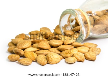 almonds nuts in glass bottle isolated on white background