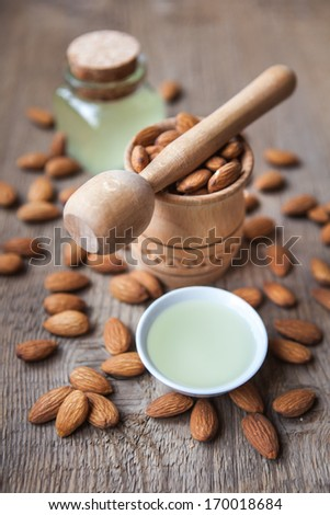 almonds oil and nuts on a wooden background - stock photo