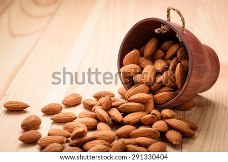 Almonds pour from wood Cup - stock photo