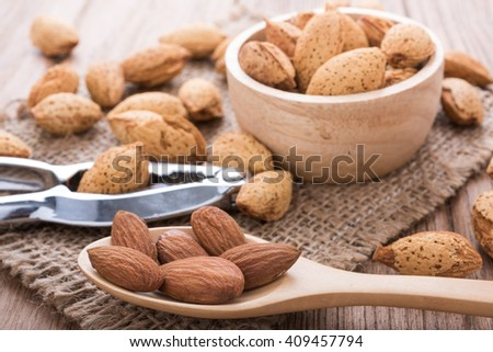 almonds set on the wooden plate, morning light - stock photo