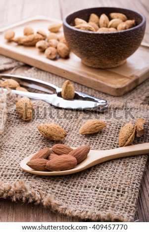 almonds set on the wooden plate, morning light,close up - stock photo