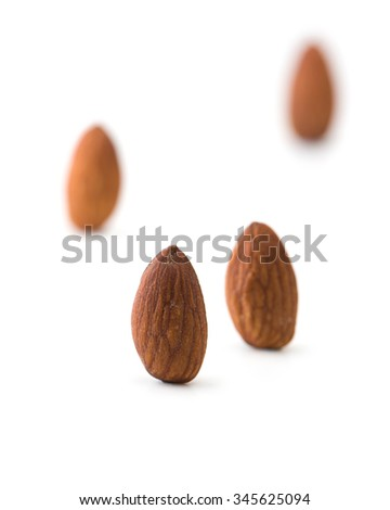 Almonds standing, isolated on white. Four almonds standing with distance between them. Shallow depth of field. - stock photo