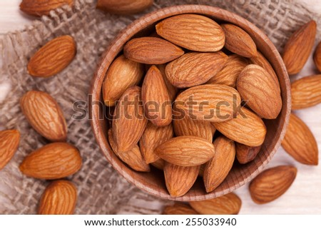 Almonds super food in a wooden dish on vintage textile background - stock photo
