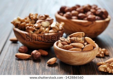 Almonds, walnuts and hazelnuts in wooden bowls  on wooden background - stock photo