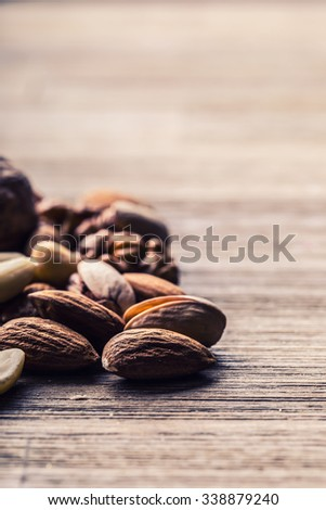 Almonds, walnuts and hazelnuts on a wooden table. Various kinds of nuts - stock photo