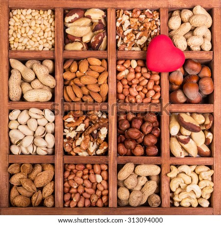 Almonds, walnuts, peanuts, cashew and hazelnuts in wooden box  background - stock photo