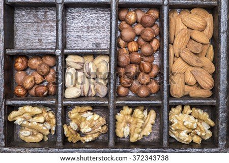 Almonds, walnuts, pistachios and hazelnuts in wooden bowls on wooden background - stock photo