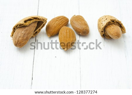 almonds, white wooden table background
