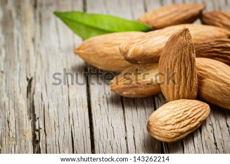 Almonds with leaf on wooden background - stock photo
