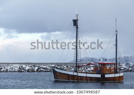 ALNES, NORWAY- January 06, 2018: Fishermen cleaning the cutter after half the fish. Marina in Alnes at Godoya Island near Alesund. Winter landscape. Norway