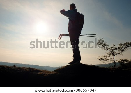 Alone adult man backpacker at sunrise at open view on mountain peak, blue sky
