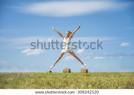 Alone blond Woman Jumping for Joy on a Grass Hill above horizon line One happy slim girl fly in a green field against blue summer sky with clouds Idea of success, growth , light, diet, luck, freedom - stock photo