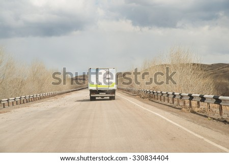 Alone clean Truck driving on clear spring asphalt road against blue sky with white clouds, empty mountain horizon with dry trees and forest along highway Back view car Idea symbol of logistics - stock photo
