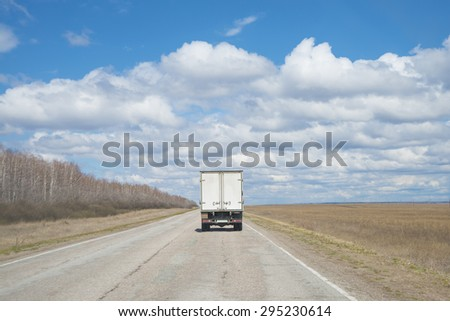 Alone Dirty Truck driving on clear spring asphalt  road against blue sky with white clouds, empty field with dry grass and forest along highway Back view car Idea symbol of logistics - stock photo
