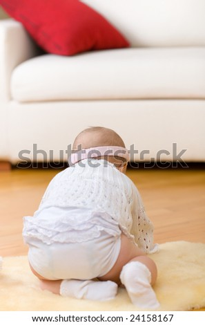 Alone little baby girl sit down on fur at hardwood floor. Rear view