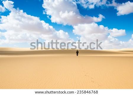 Alone man in the Sahara desert in Egypt - stock photo