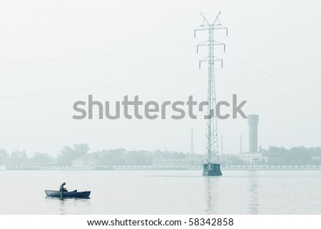 Alone man sitting in a boat in an industrial zone