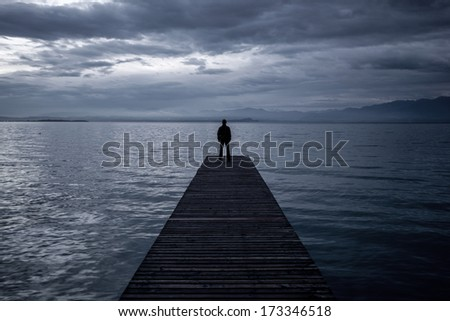Alone man standing on the edge of a pier in twilight - stock photo