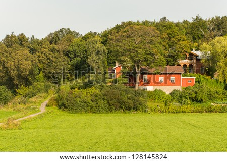 Alone red farmhouse on a meadow in forrest - stock photo