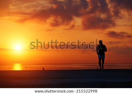 Alone runner at morning jog on beautiful background of colorful sunrise sky, spot training outdoors, back view of male sportsman running on the beach, fitness and healthy lifestyle concept