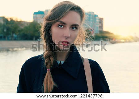 Alone thinking. Front view image of a young beautyful women posing outdoors against river and urban skyline alone with blank expression on her face - stock photo