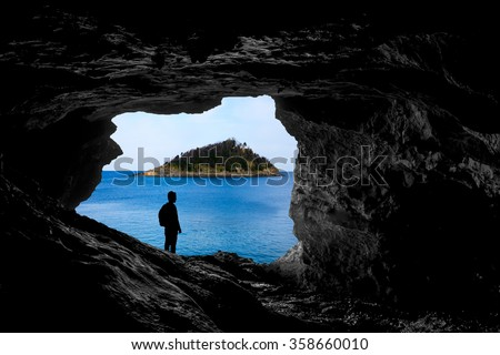 Alone traveller into a cave look a beautiful island from inside a cave, backlight silhouette, discovering new places